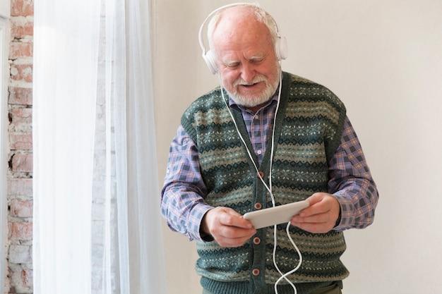 Älterer spielender musik des niedrigen winkels am telefon