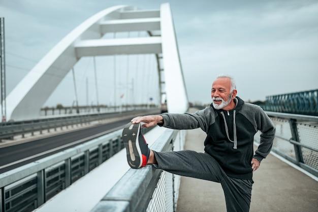 Älterer sportler, der draußen, auf die stadtbrücke ausdehnt.