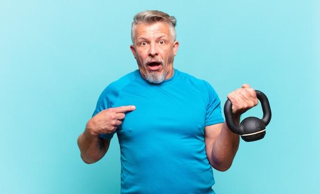 Älterer sportler, der schockiert und überrascht mit weit geöffnetem mund aussieht und auf sich selbst zeigt