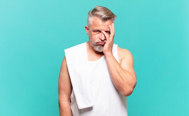 Älterer sportler, der sich nach einer ermüdenden, langweiligen und mühsamen aufgabe gelangweilt, frustriert und schläfrig fühlt und das gesicht mit der hand hält