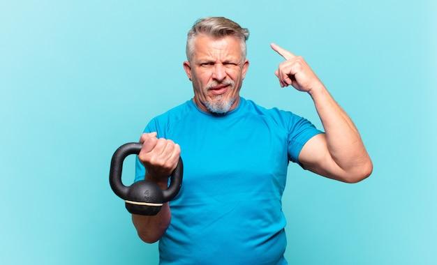 Älterer sportler, der sich verwirrt und verwirrt fühlt und zeigt, dass sie verrückt, verrückt oder verrückt sind