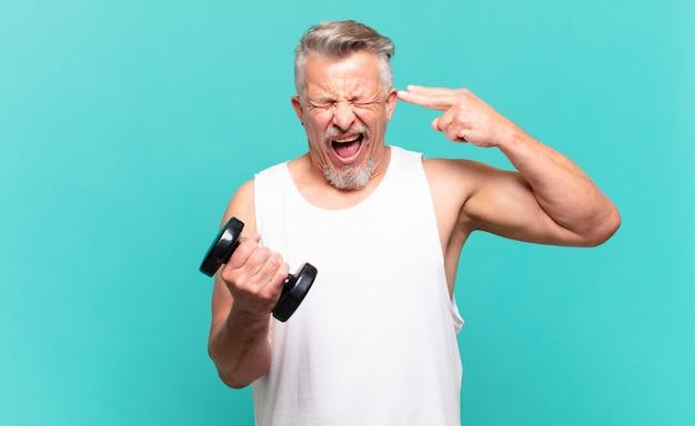 Älterer sportler, der unglücklich und gestresst aussieht, selbstmordgeste, die waffenzeichen mit der hand macht und auf den kopf zeigt
