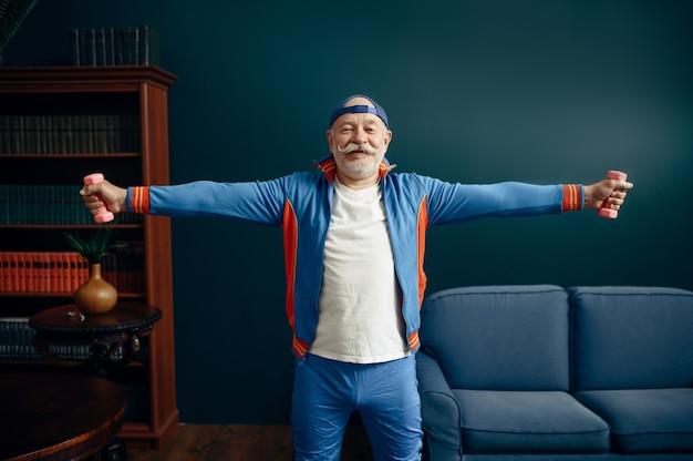 Älterer sportler in uniform, der zu hause mit hanteln trainiert. erwachsene männliche person beim fitnesstraining drinnen, gesunder lebensstil im alter old
