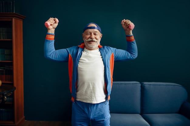 Älterer sportler in uniform, der zu hause mit hanteln trainiert. erwachsene männliche person beim fitnesstraining drinnen, gesunder lebensstil