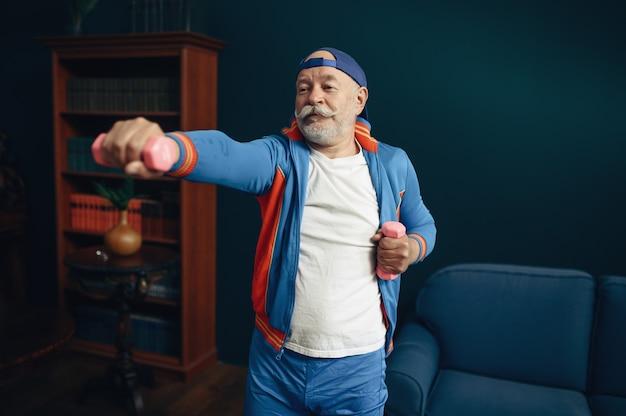 Älterer sportler in uniform, training zu hause. erwachsene männliche person beim fitnesstraining drinnen, gesunder lebensstil im alter old