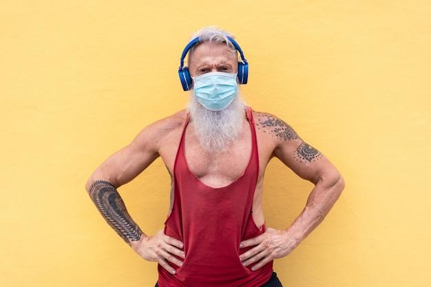 Älterer sportlermann, der medizinische gesichtsmaske für coronavirus-prävention beim hören von wiedergabelistenmusik trägt