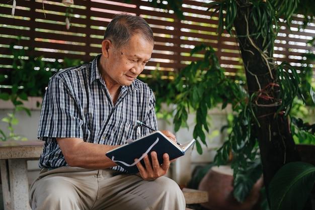 Älterer thailändischer mann, der auf marmorstuhl unter dem baum sitzt und notizen schreibt, konzept der alzheimer-krankheit.