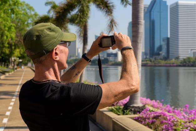 Älterer touristenmann, der kappe trägt, während fotos bei friedlich macht