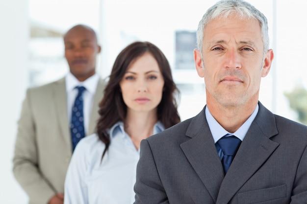 Älterer und ernster manager, der aufrecht steht und von zwei angestellten gefolgt wird