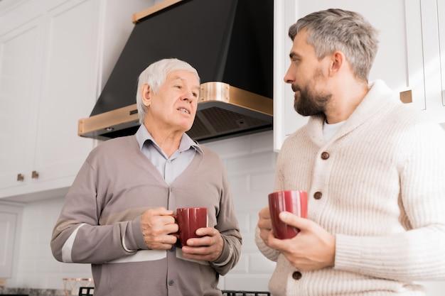 Älterer vater im gespräch mit dem erwachsenen sohn
