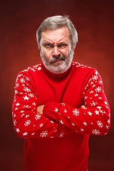 Älterer verärgerter mann in einem roten weihnachtspullover