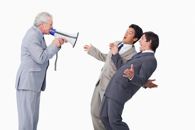 Älterer verkäufer mit dem megaphon, das an seinen angestellten schreit