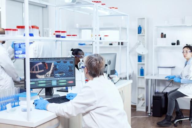 Älterer virologe, der an einem computer mit viren arbeitet, die in einer modernen einrichtung ausgestellt sind. leitender wissenschaftler im pharmazeutischen labor, der genetische forschung mit laborkittel mit team im hintergrund durchführt.