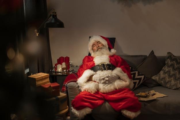Älterer weihnachtsmann, der auf der couch schläft
