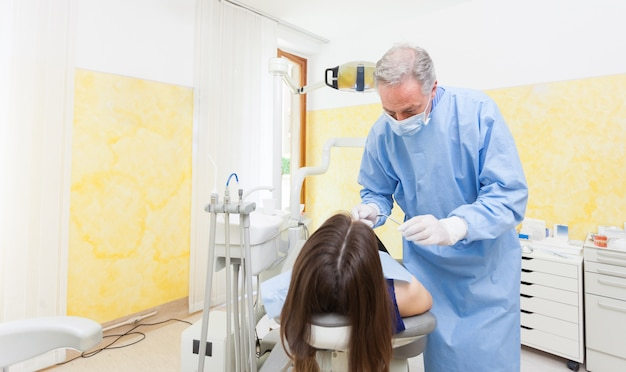 Älterer zahnarzt, der einen weiblichen patienten kuriert