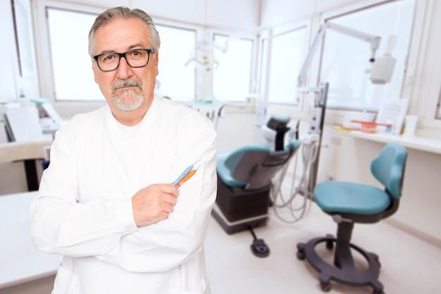 Älterer zahnarzt, der in ihrem büro steht
