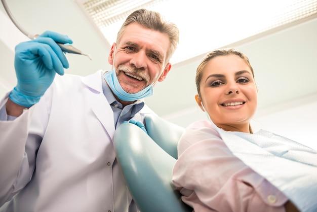 Älterer zahnarzt mit seinem weiblichen kunden in der zahnmedizinischen klinik.