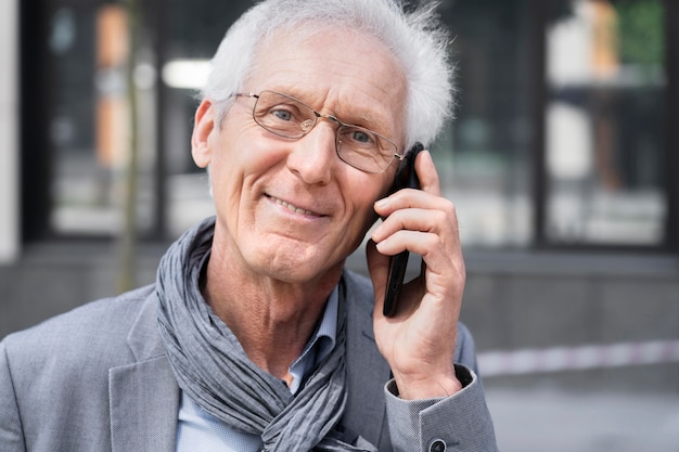 Älterer zufälliger mann in der stadt, der auf smartphone spricht