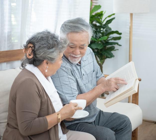 Älteres älteres asiatisches paar, das zusammen auf dem sofa-lesebuch zu hause sitzt