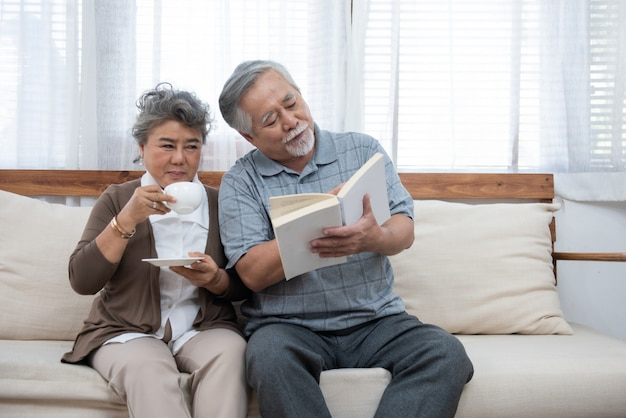 Älteres älteres asiatisches paar, das zusammen auf dem sofa sitzt und buch zu hause liest. großmutter und großvater im ruhestand verbringen zeit zusammen im haus.