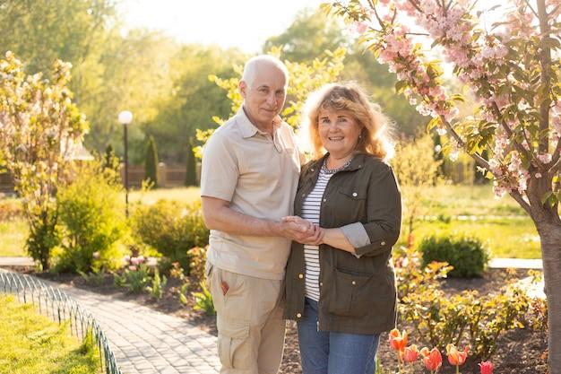 Älteres älteres kaukasisches paar zusammen im park im frühjahr oder sommer. frau, die ehemannlächeln mit glück umarmt. schöne liebesbeziehung und pflege von alten menschen im ruhestand.
