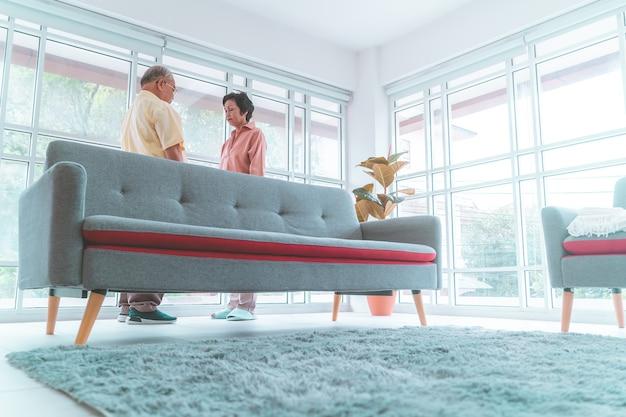Älteres asiatisches ehepaar steht im wohnzimmer bereit für romantische liebe, die zusammen tanzt.