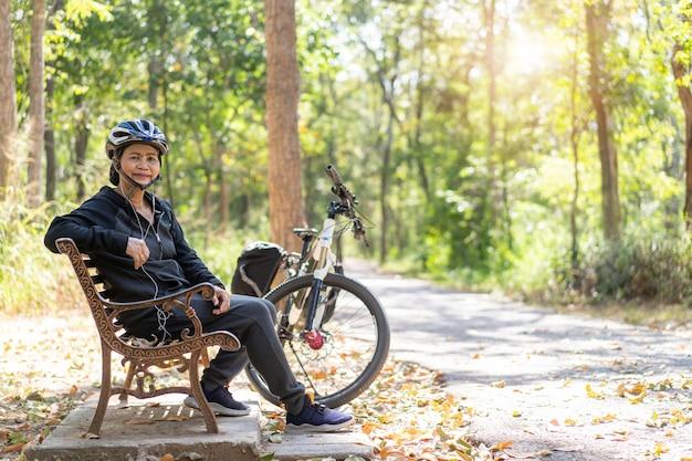 Älteres asiatisches frauenfahrrad mit im park sitzend