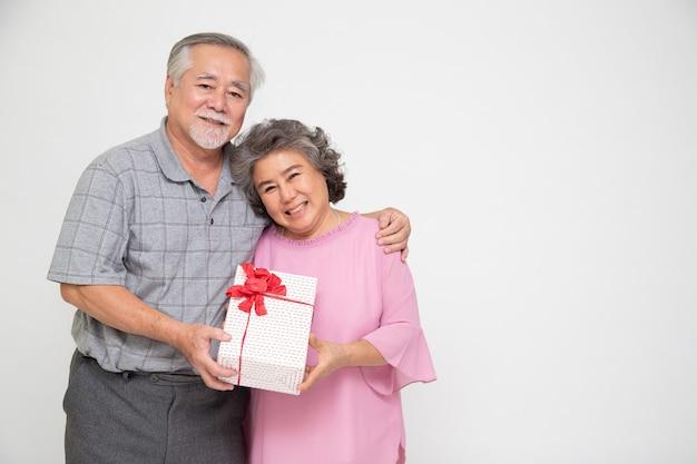 Älteres asiatisches paar, das geschenkbox lokalisiert auf weißem hintergrund hält