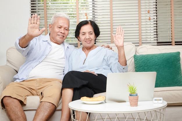 Älteres asiatisches paar, das im wohnzimmer sitzt heben sie ihre hand, um kinder und enkelkinder über online-video auf dem laptop zu begrüßen