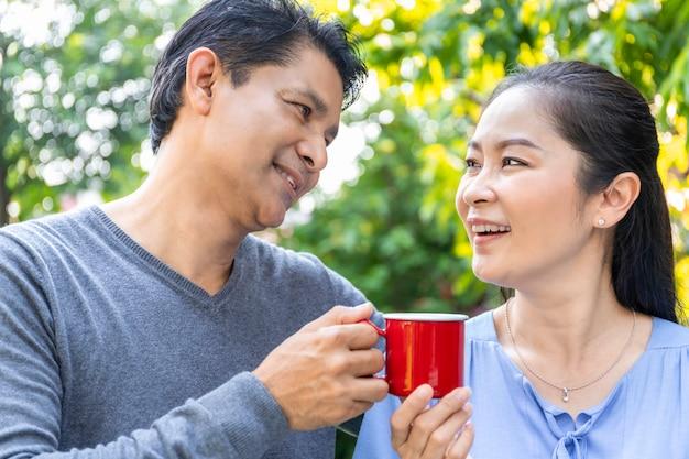 Älteres asiatisches paar, das kaffee am garten trinkt.