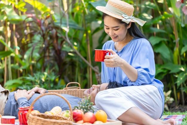 Älteres asiatisches paar, das kaffee und picknick im garten trinkt.