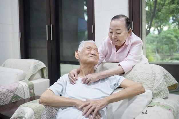 Älteres asiatisches paar, das sich auf dem sofa umarmt