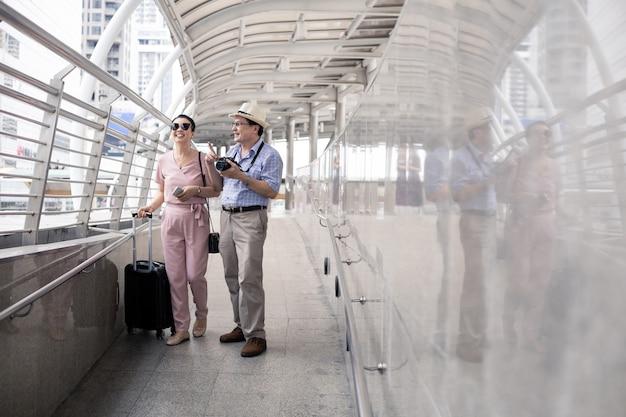Älteres asiatisches paar mit einer frau, die einen koffer schleppt und glücklich mit dem lächeln am flughafen spricht, um sich auf die reise vorzubereiten. glück von tanten und onkeln auf reisen reisen zusammen mit einem lächeln.