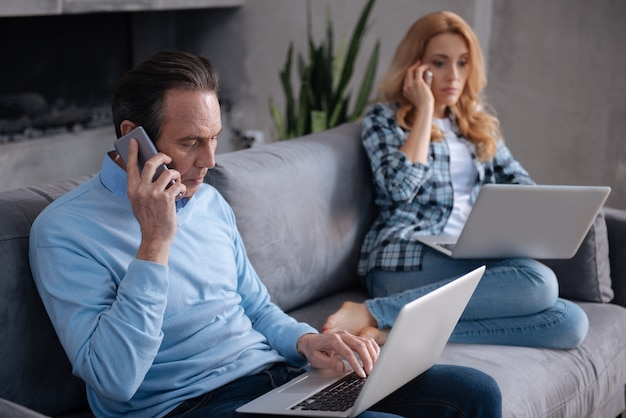 Älteres, beschäftigtes, geschicktes paar, das zu hause auf der couch sitzt und elektronische geräte verwendet, während es im internet surft und geschäftsgespräche führt