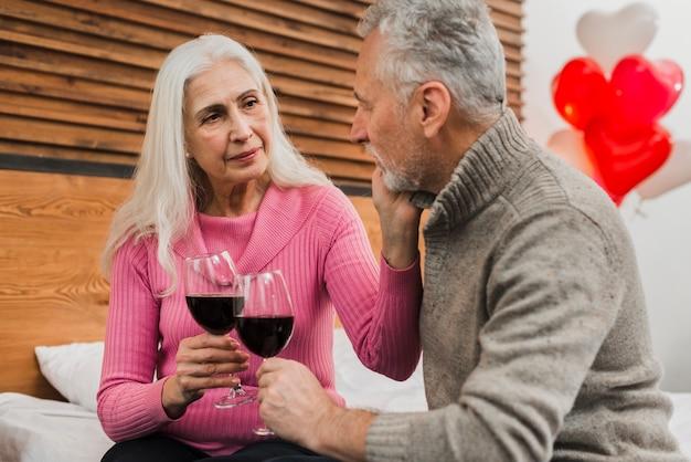 Älteres ehepaar auf bett wein trinken
