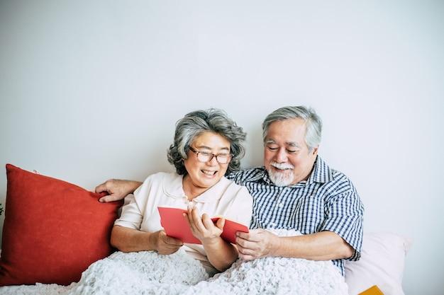 Älteres ehepaar auf dem bett liegend und ein buch zu lesen