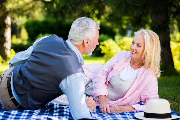 Älteres ehepaar auf eine decke legen