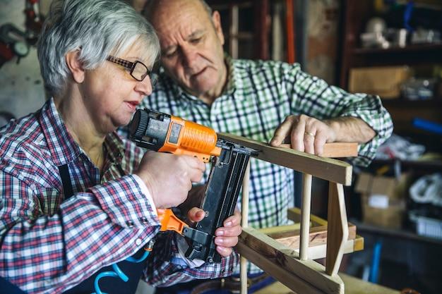 Älteres ehepaar, das in einer tischlerei arbeitet
