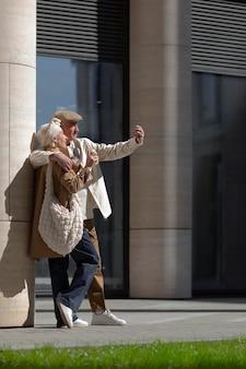 Älteres ehepaar draußen in der stadt, das kaffee trinkt und ein selfie macht
