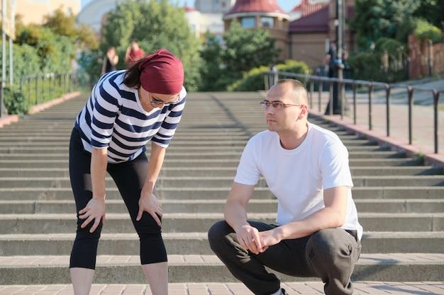 Älteres ehepaar in der stadt in der nähe der treppe, mann mittleren alters und frau in sportbekleidung