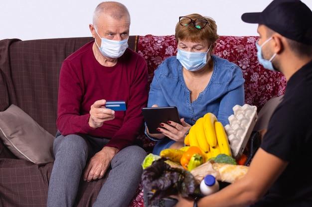 Älteres ehepaar in gesichtsmaske, das lebensmittel von einem freiwilligen liefermann erhält, der sich während des virusausbruchs um die ältere familie kümmert, hilft beim einkaufen bei der zahlung mit kreditkartensignatur auf dem tablet