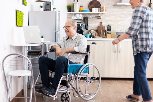 Älteres ehepaar lacht mit laptop, ehemann ruft seine frau während eines videoanrufs in seiner nähe an, während die enkel in der küche sitzen. gelähmter behinderter alter älterer mann mit kommunikationstechnologie