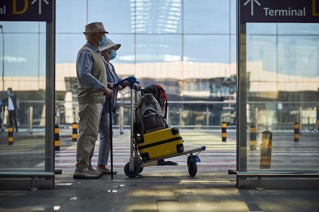 Älteres ehepaar mit gepäck in die ferne blicken