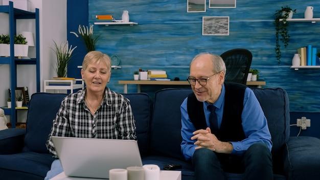Älteres ehepaar sitzt auf dem sofa und winkt während des videoanrufs in die kamera