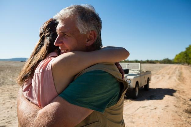 Älteres ehepaar umarmt auf dem feld