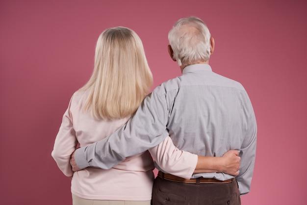 Älteres ehepaar umarmt sich von hinten.
