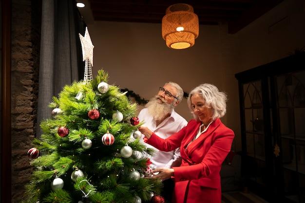 Älteres ehepaar weihnachtsbaum einrichten