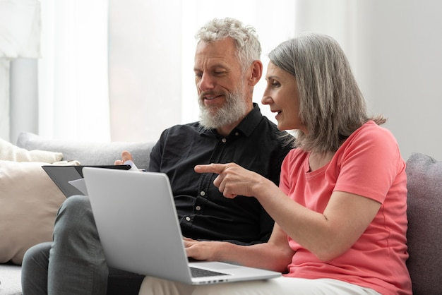 Älteres ehepaar zu hause auf der couch mit laptop
