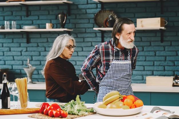 Älteres europäisches rennpaar, das in der küche schürzen anzieht
