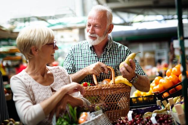 Älteres familienpaar, das beim wöchentlichen einkauf bio-obst und -gemüse auf dem markt wählt